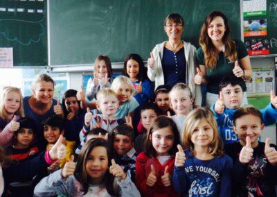 Gabriela, Edinho e Brigitte com crianças após palestra