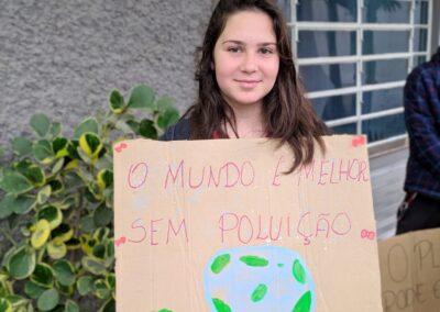 """""""O Mundo é melhor sem poluição"""", diz cartaz nas mãos da jovem.  Foto: Arquivo Plantando o Futuro."""